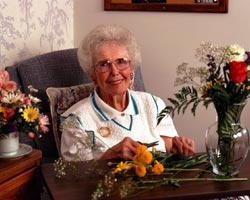 A senior woman making a flower arrangement.
